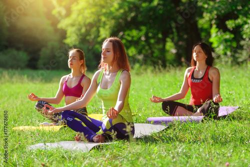 Naklejka Girls posing yoga outside in the forest in the morning