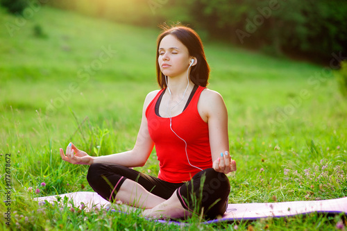 Wall mural Girl posing yoga outside in the forest in the morning