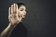 Serious woman gesturing to stop isolated on a black background