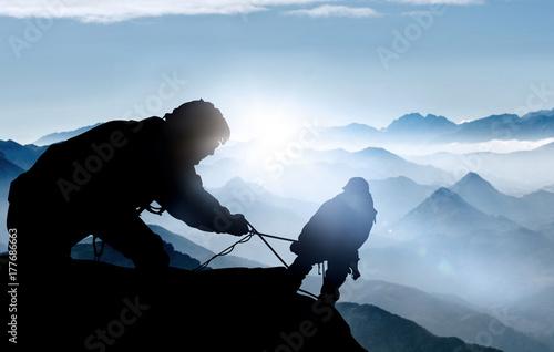 Hilfe beim Aufstieg - Bergsteiger auf einem Gipfel