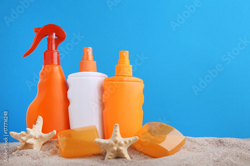 Sunscreen bottles with starfish on beach sand