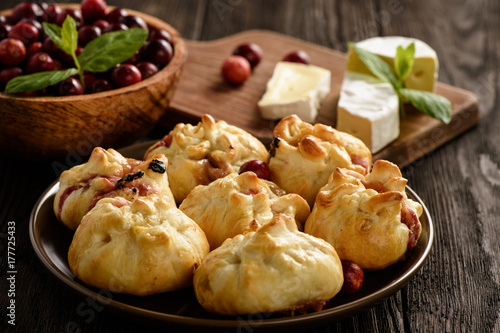 Poster Puff pastry pies with camembert cheese and cranberries.