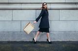 Stylish female shopper walking with shopping bag - 177728697