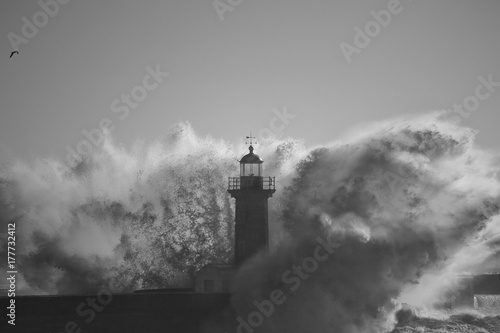 Lighthouse in the middle of stormy waves splash