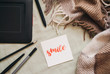 Flat lay of artist home office in bed. Handwritten word Smile on a paper card