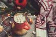 christmas table top view with hot cocoa, warm knitted sweater and garland. Cozy winter morning at home
