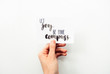"Minimal composition on a white background with girl's hand holding card with inspirational quote ""let joy be your compass"" written in calligraphy style"