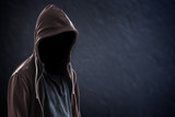 Silhouette of man with a hood and face in the dark, black background with copy space, criminal or hacker concept - 177746835
