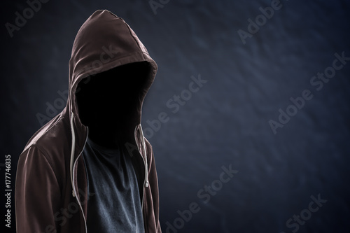 Silhouette of man with a hood and face in the dark, black background with copy s Plakát