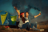Young happy couple holding smoke bombs on camping - 177749881