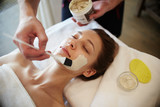 Portrait of beautiful young woman in SPA, lying on massage table enjoying face masks and beauty treatments, with male hands applying clay cream