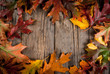 Autumn concept, background, old rustic wooden table with red and yellow leaves, top view, frame