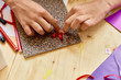 Closeup image of little girls hands putting bow to handmade gift card during art and craft lesson in school