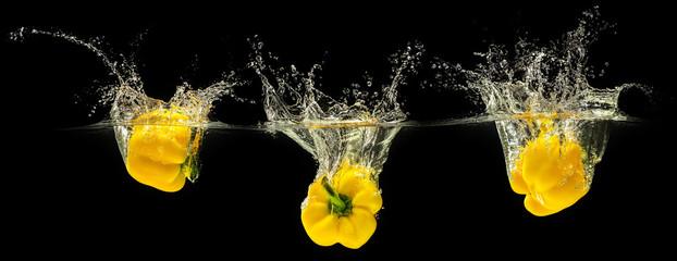 Yellow bell pepper falling in water