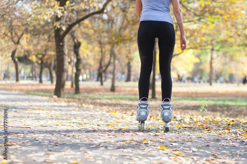behind view of young woman on roller blades in autumn park Poster