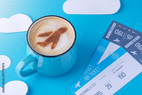 Cup of cappuccino with a picture of the plane on the foam and tickets. Blue sky background with paper clouds