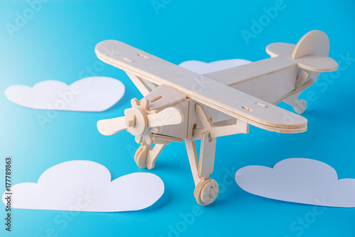 Wooden toy airplane on a background of blue sky with paper clouds. Concept travel and airlines