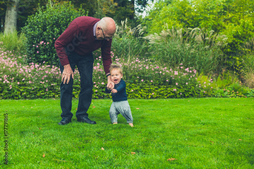 Grandfather running with grandson on lawn Poster
