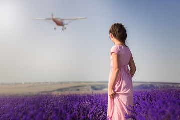 girl stands in lavender and looks at the plane