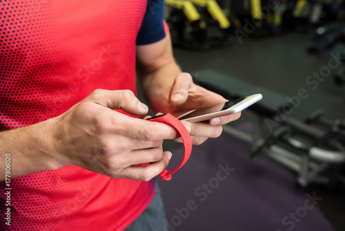 Poster Closeup of strong male hands setting up fitness bracelet checking data on smartphone while working out in modern gym, copy space