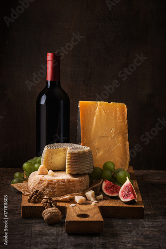 Fototapeta Cheese board, fruits and wine on the rough wood