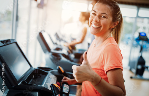 Wall mural Young attractive woman doing cardio training in gym