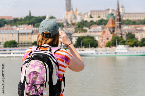 A female tourist with a backpack takes a photograph of Buda Castle in Budapest Poster
