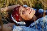 Closeup of young woman listens to music and lying in the meadow - 177831245