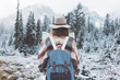 Traveling woman standing in the wild with map in front of amazing view. Wearing hat, poncho and backpack. Winter is coming, first snowfall. Wanderlust and boho style
