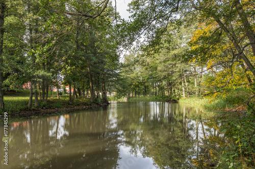Natur runt Åkersa kanal med stora ekar och det lugna vattnet i kanalen med gångvägar, konst, fritidsbåtar och vackra plattser Poster