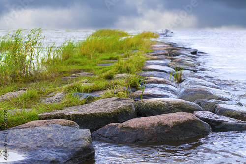 Fotobehang Pier Closeup on the rocks of a natural breakwater