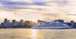 Cruise boat sailing at sunset on St. Lawrence River with skyline of Montreal on the background, Canada