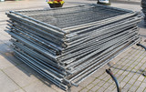 A stack of modular steel fence elements made of galvanized steel grating. - 177886820