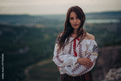 Atractive woman in traditional romanian costume on mountain green blurred background. Outdoor photo. Traditions and cultural diversity © Yuriy Seleznyov