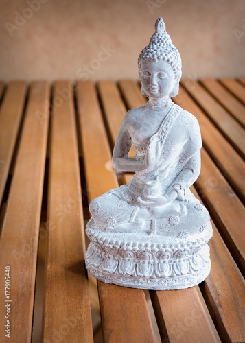 Foto op Canvas Boeddha White Buddha statue on wooden background with copy space. Inspiration sculpture for meditation or mindfulness.