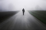 Man walking alone on rural misty asphalt road - 177919855