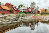 Typical Swedish fishing village with red wooden houses. - 177931633