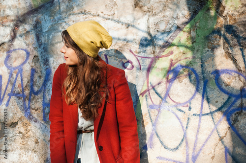 Modern girl in autumn seasson, walking around the city in the beautiful sunset light over graffiti wall background Poster