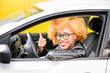 Portrait of a beautiful african woman in leather jacket sitting in a car on the yellow background
