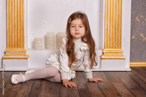 Young brunette dolly lady girl stylish dressed in white skirt midi petticoat and waist blouse smiling posing in studio close to chimney place grate with pout lips and pink cheeks Poster