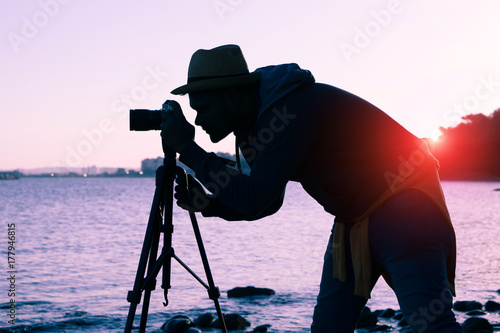 Silhouette of photographer at sunset on the beach using camera on tripod - Conce Poster