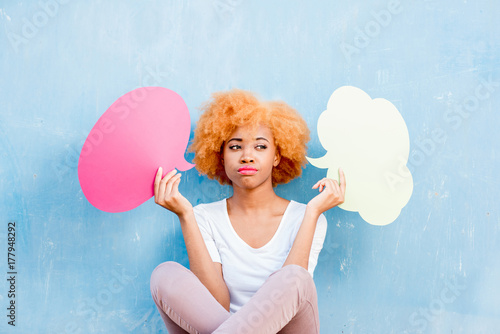 Beautiful african woman holding colorful thoughtful bubbles on the blue wall bac Poster