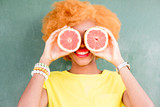 Portrait of a beautiful african woman with grapefruit slices on the green wall background
