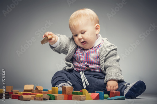 Toddler boy playing with building blocks. Poster