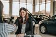 Saleswoman shaking hands with customer in car salon.