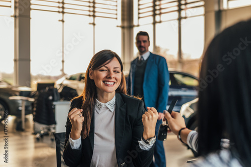 Cheerful young woman receiving new car keys in car shop.
