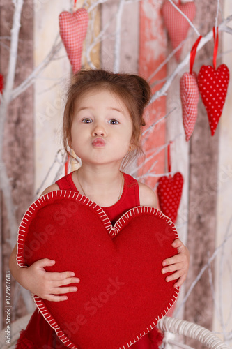Young brunette dolly lady girl stylish dressed in red dress strap shoes smiling posing sitting in studio and holding big huge heart with pout lips and pink cheeks Poster