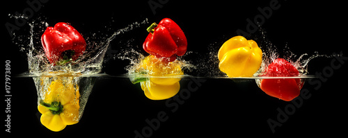 Group of bell pepper falling in water