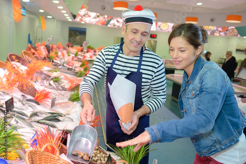 Fototapeta Fishmonger serving shellfish to customer