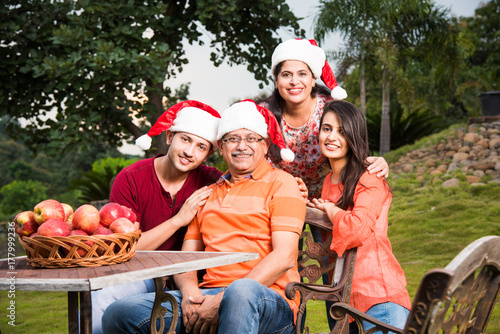 Indian family celebrating christmas and posing for a group photo Poster